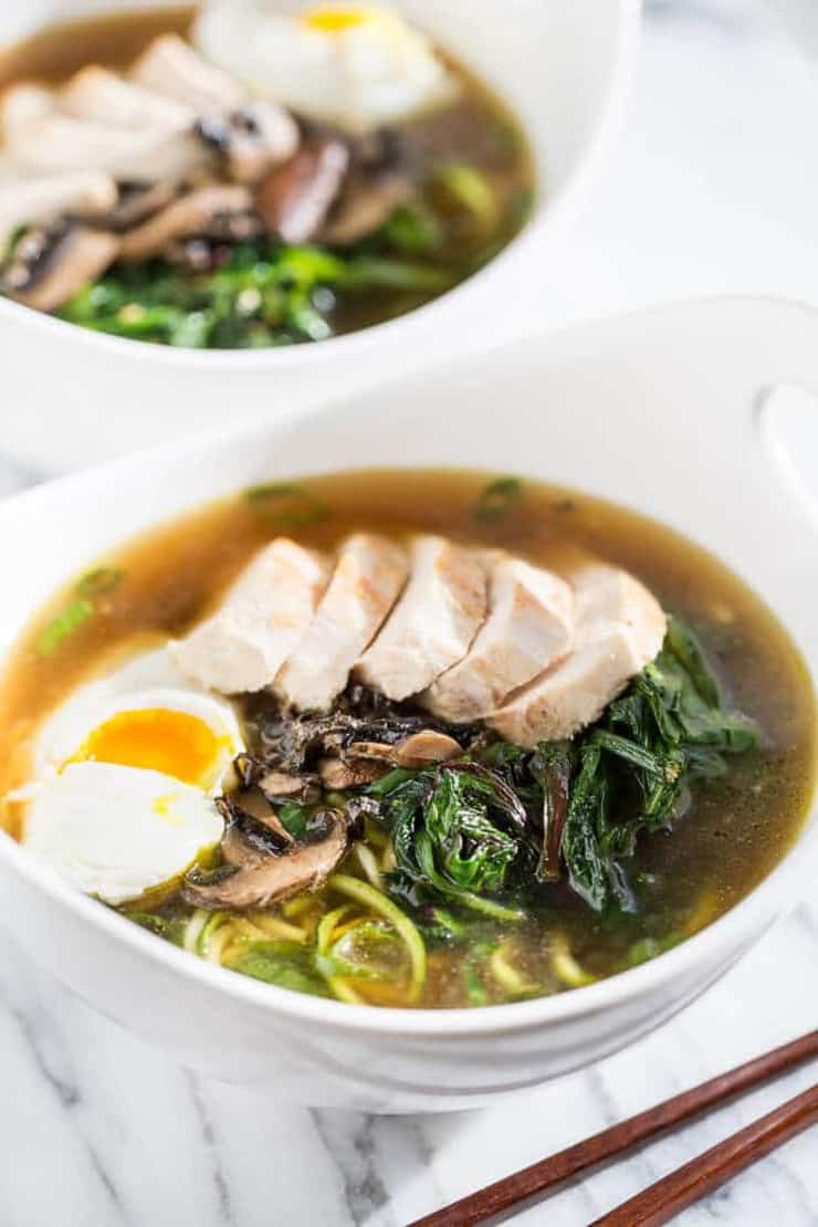 A bowl of chicken ramen with egg, greens and noodles