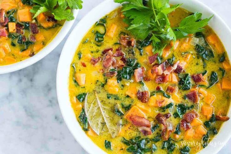 A bowl of sweet potato soup topped with bacon and herbs