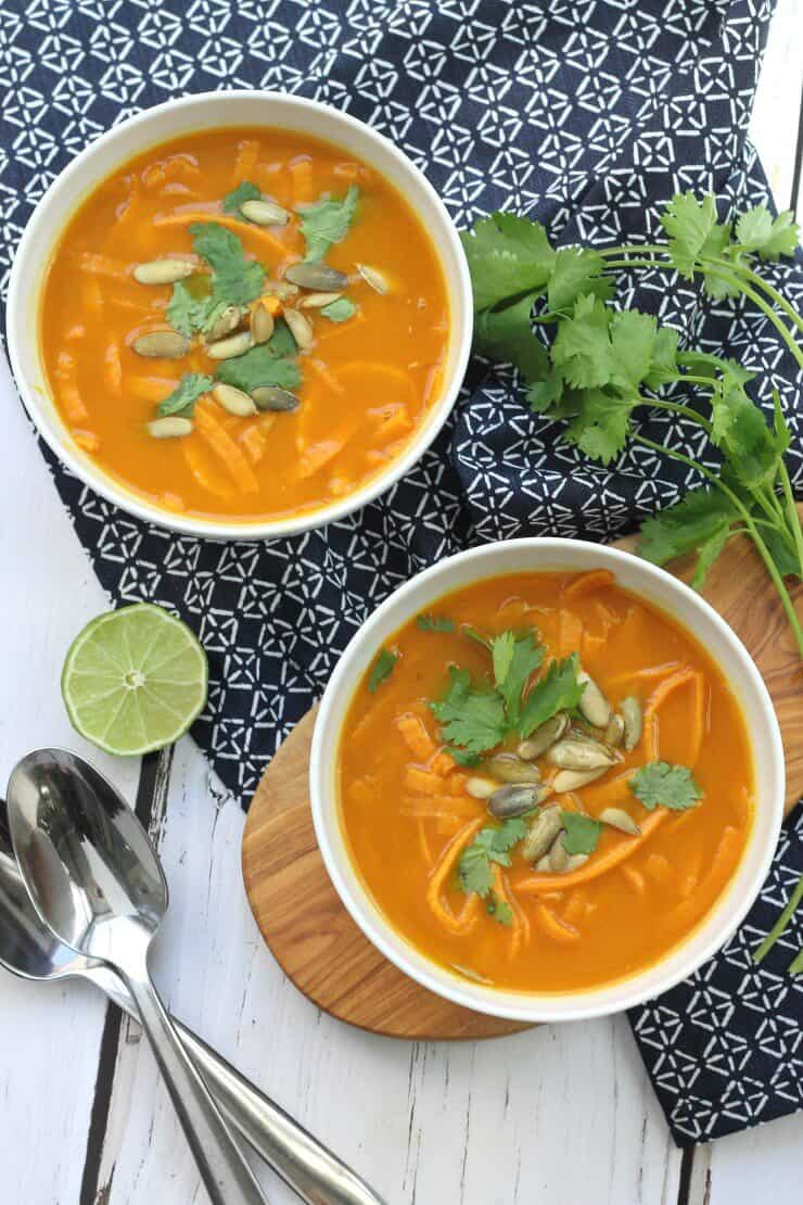 Tow bowl of pumpkin curry soup topped with pumpkin seeds