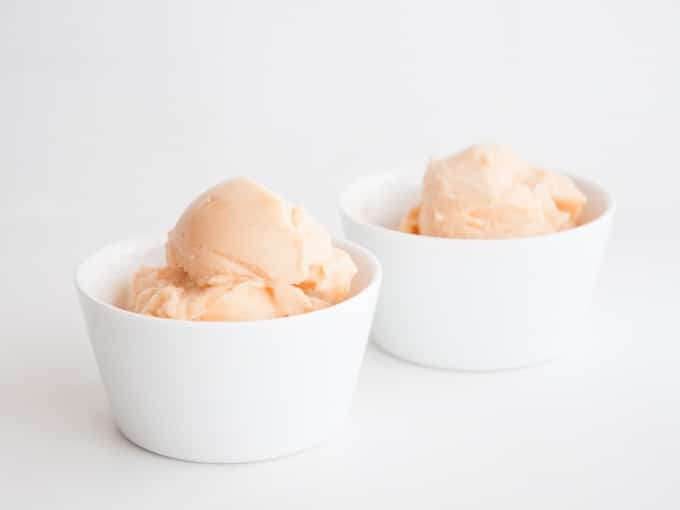 Two white cups of peach colored Cantaloupe Ice Cream with white background