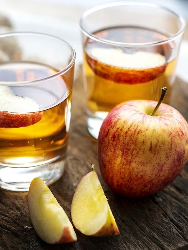 Glass of apple cider with slices of apple in it on wooden table