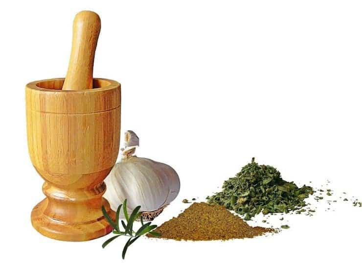 Wooden mortar and pestle next to garlic and herbs
