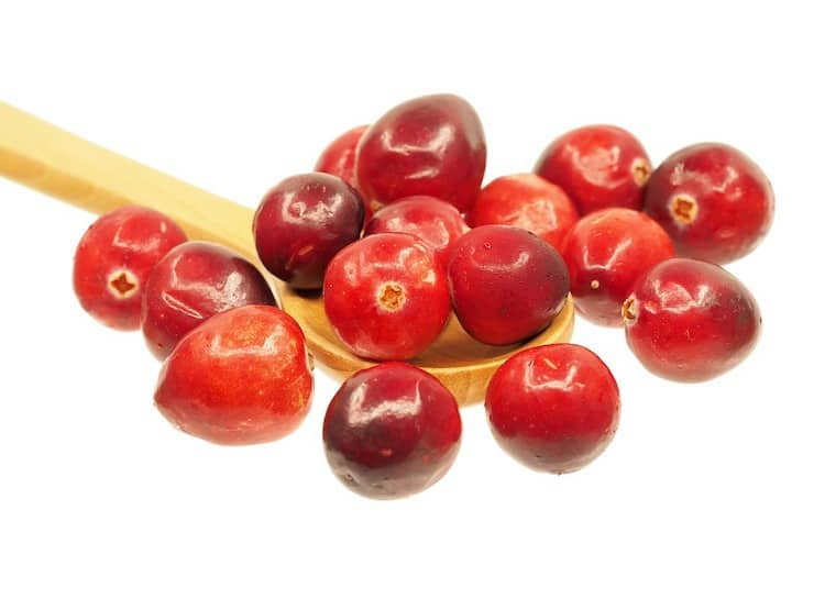 Red cranberries on a wooden spoon on a white surface