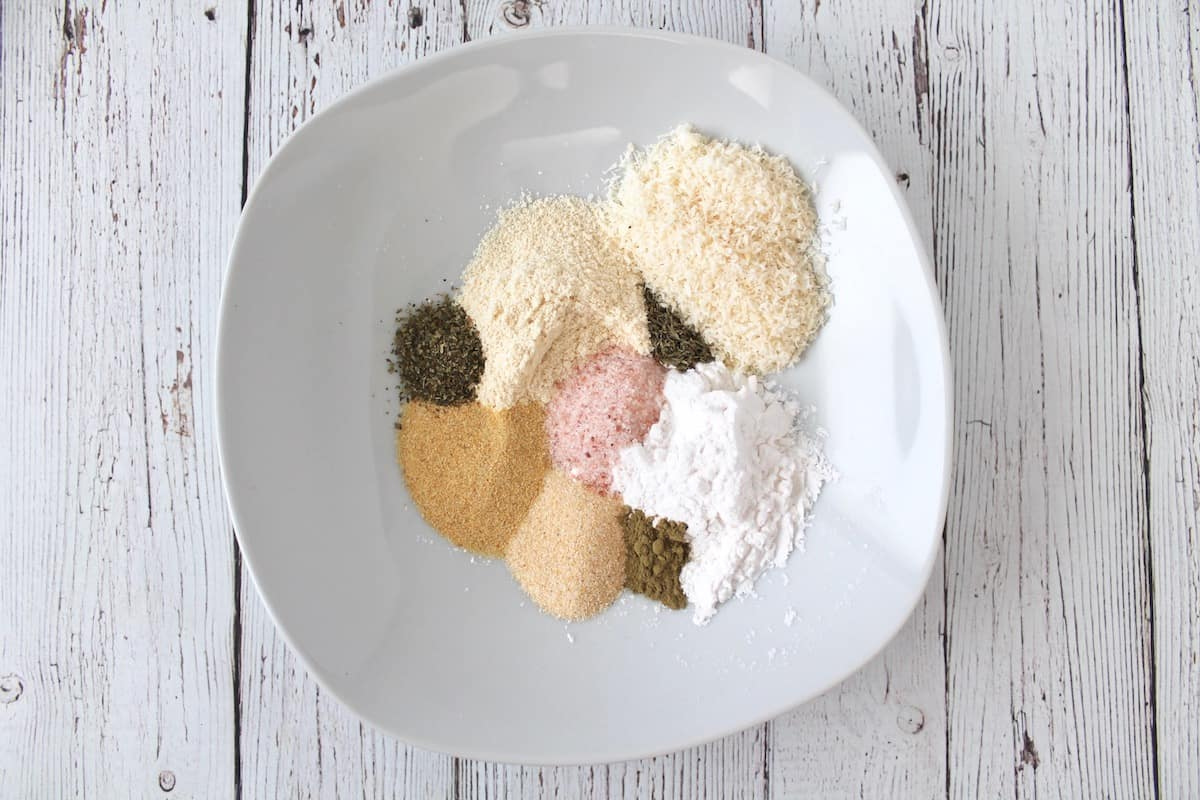 Overhead shot of a white shallow bowl with various colored heaps of spices and flours on a white wooden surface