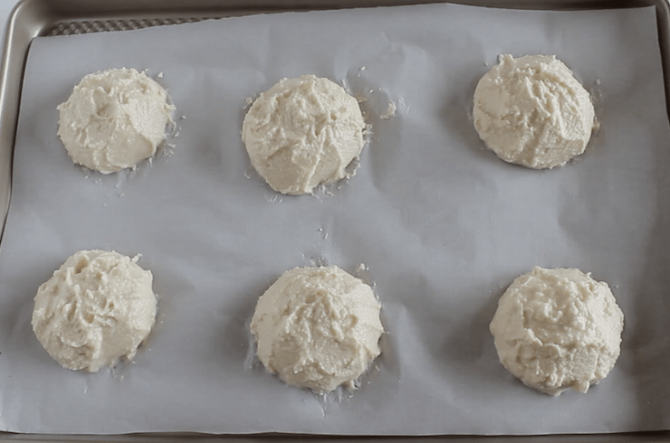 Paleo biscuit dough in 6 heaps on a baking sheet lined with white parchment paper