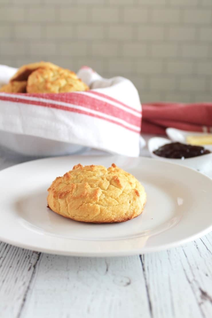 one yellow paleo biscuit on a white plate with bowl full of biscuit in background