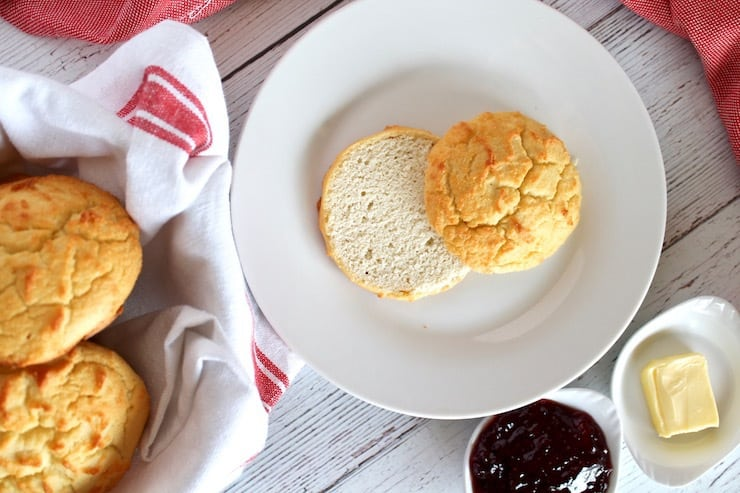 overhead view of one paleo biscuit cut in half on a white plate next to a bowl of biscuits