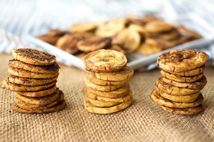 Three stacks of plantain chips with a plateful in the background