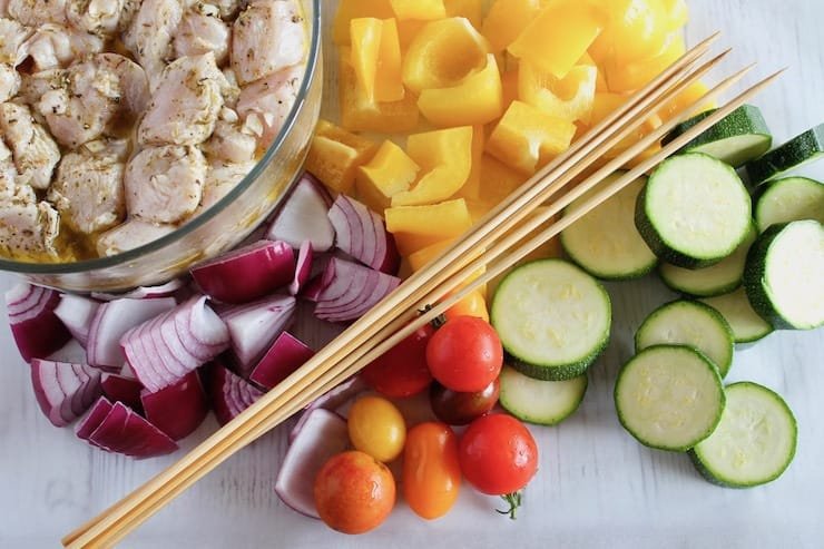 Chopped colorful vegetables next to bowl of marinated raw chicken with wooden skewers on top