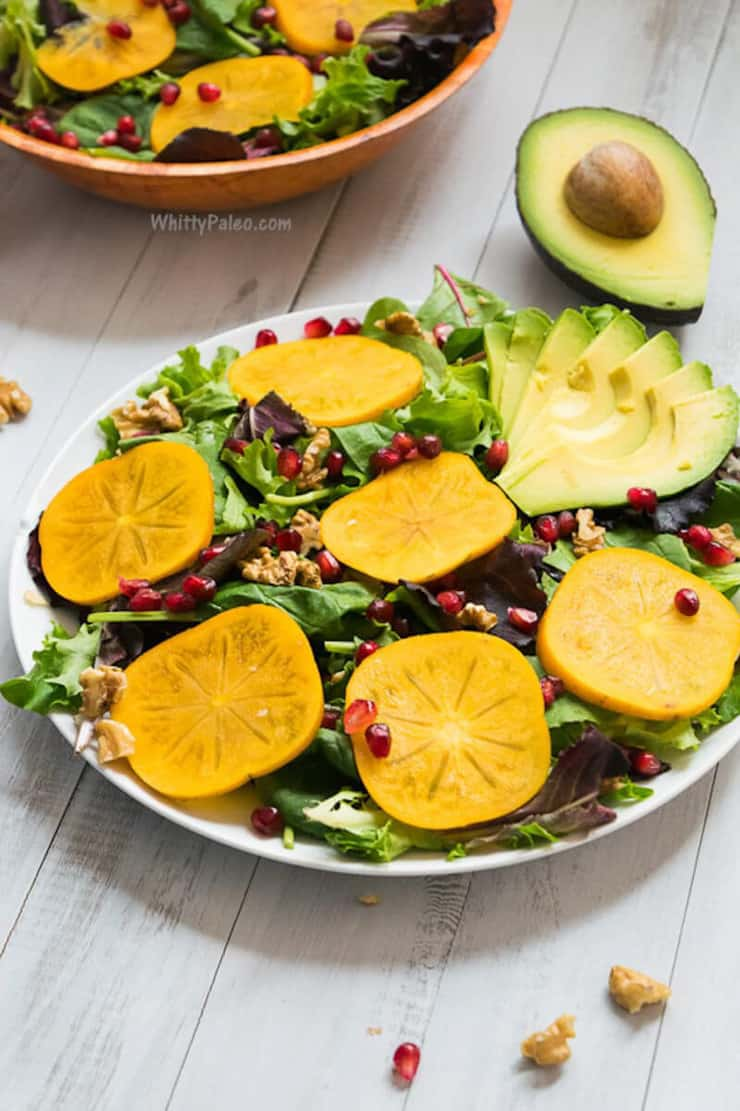 A salad on a white plate with persimmons, pomegranate and avocado