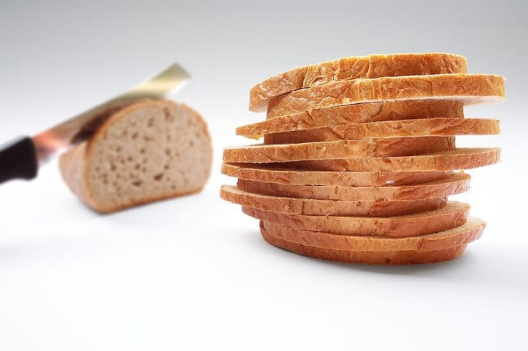A pile of sliced bread sitting on a work surface