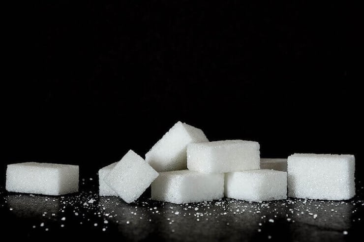 sugar cubes in a small pile on a black surface
