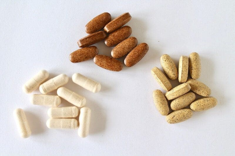 three groups of different colored vitamins on a white table