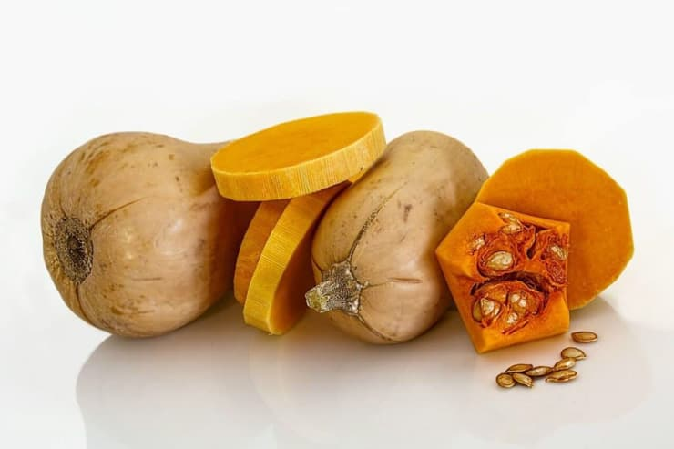 Slices of butternut squash on a white surface