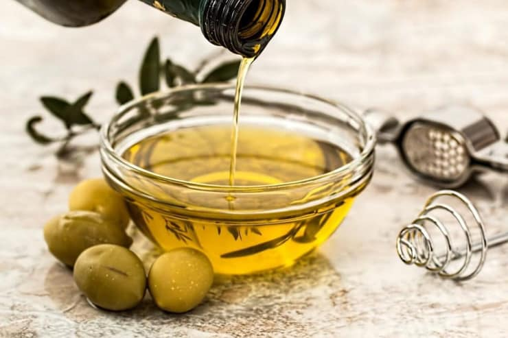 A small glass bowl of olive oil with olives at the side