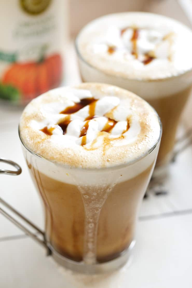 Two clear mugs filled with pumpkin latte with white foam top drizzled with caramel on a white table