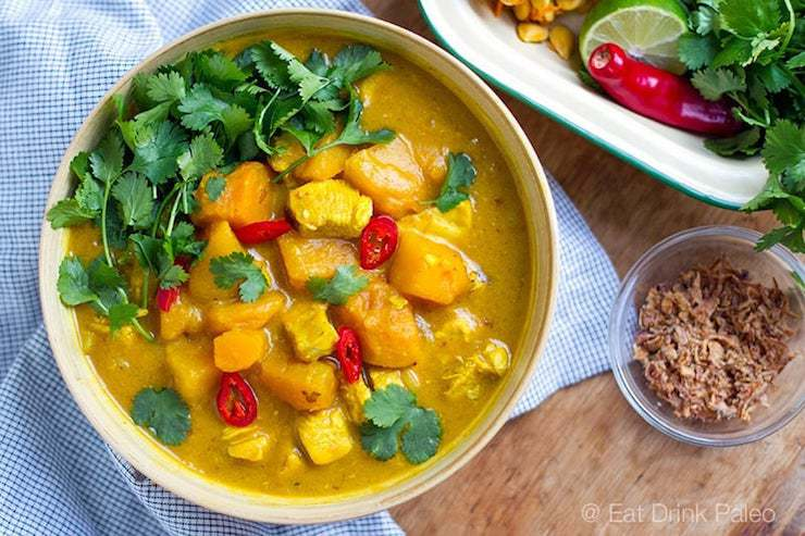 Overhead shot of orange pumpkin curry with chunks of pumpkin, cilantro and peppers