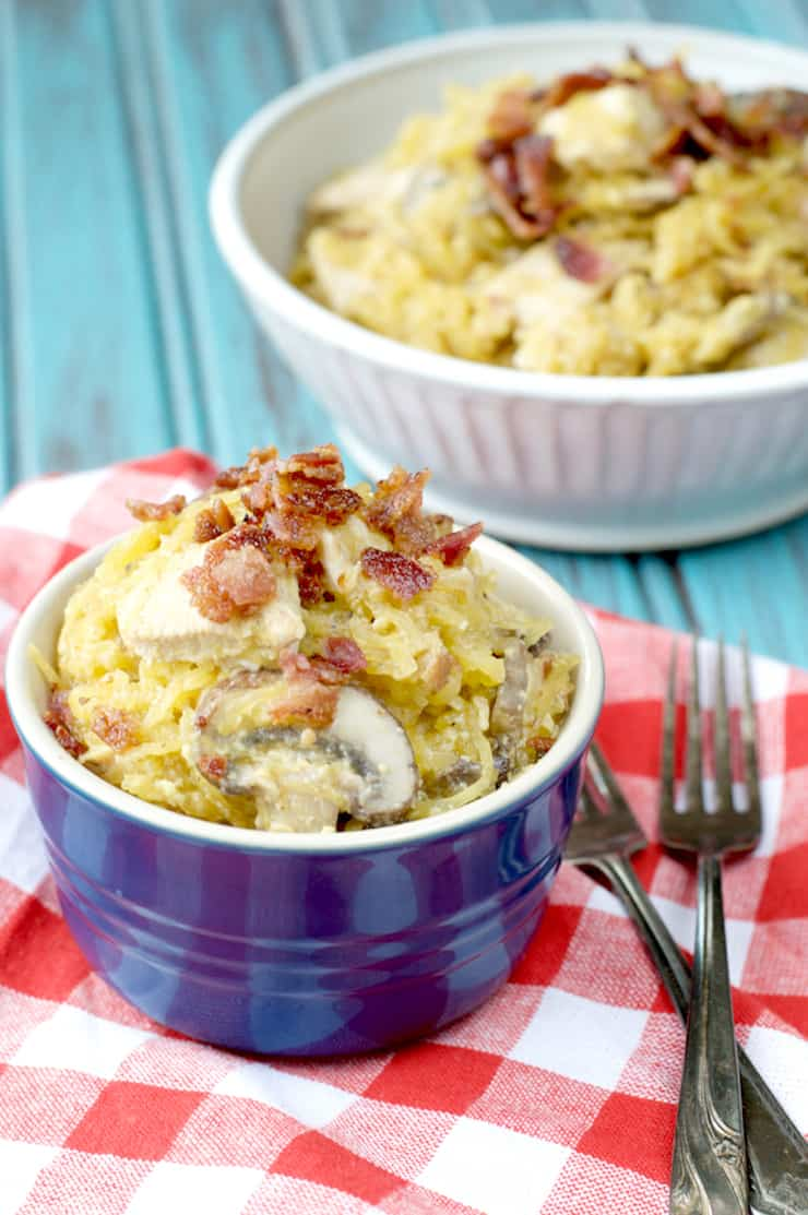 Small blue ramekin filled with spaghetti squash pasta topped with bacon crumbles