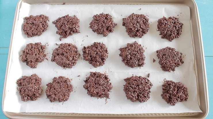 Heaps of chocolate coconut mixture on white parchment paper on a baking sheet
