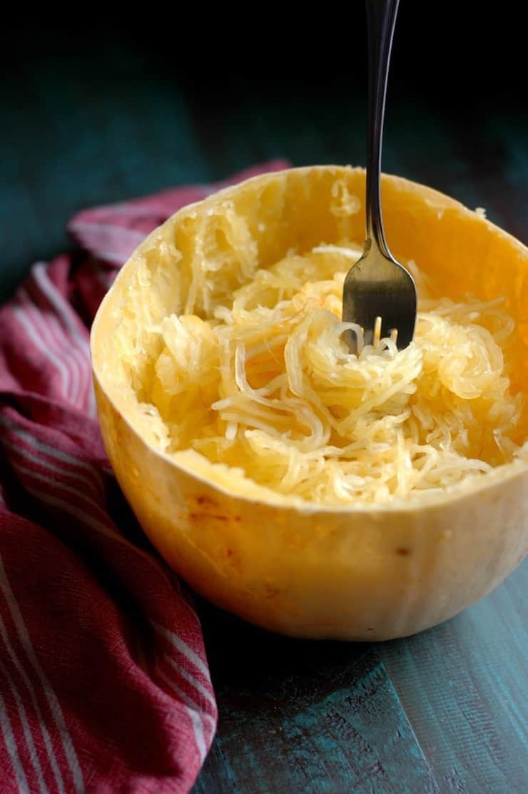 Halved spaghetti squash cooked with loosened tendrils inside and a fork