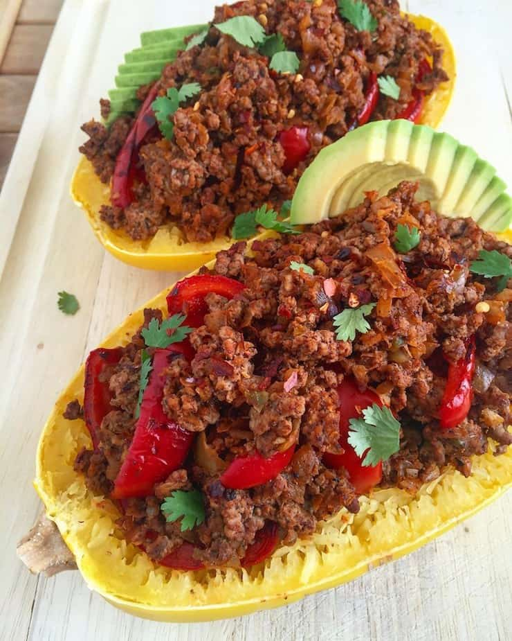 Halved cooked spaghetti squash filled with heaping beef and pepper and avocado