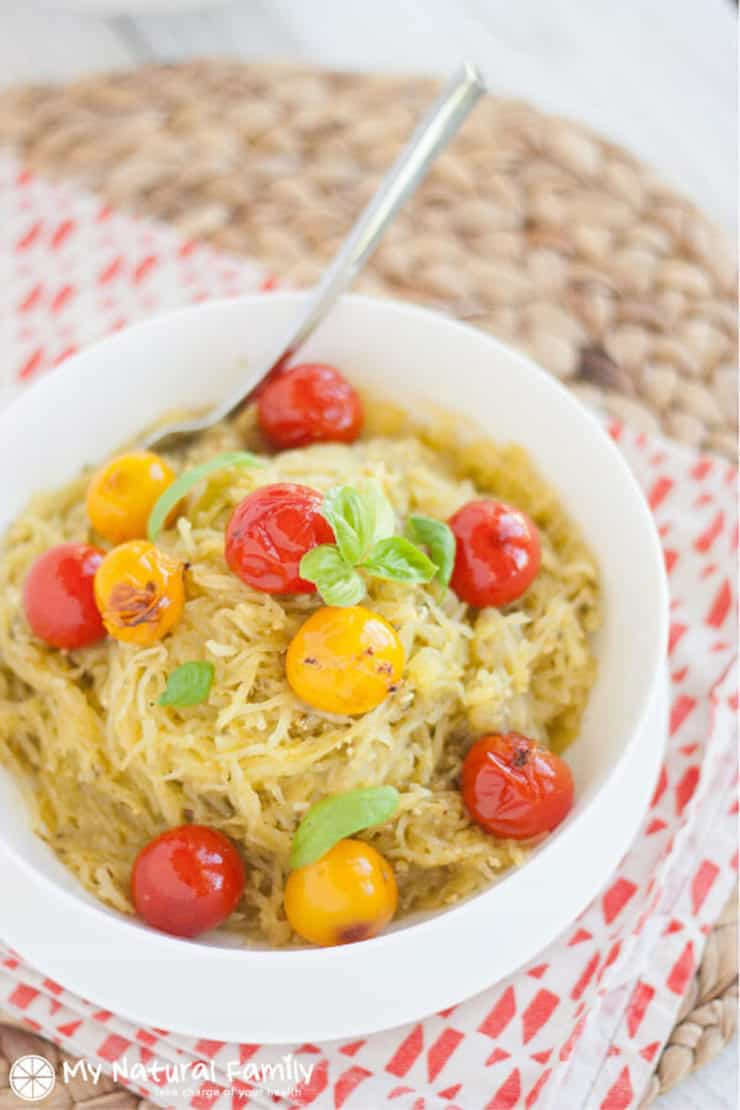 White bowl filled with yellow spaghetti squash and grape tomatoes