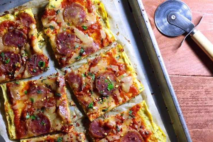 Metal baking sheet with square-cut pizza crust made from spaghetti squash topped with tomato sauce, cheese and pepperoni