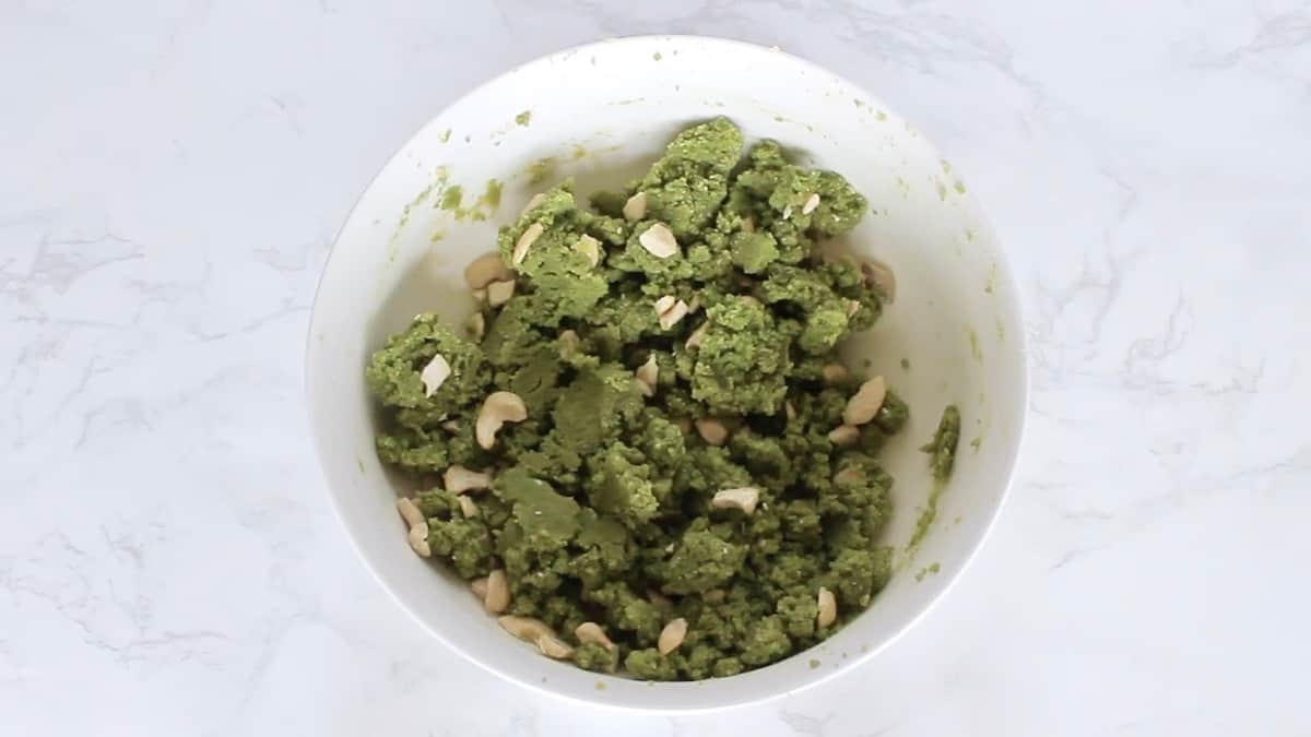 Green matcha cookie dough with cashews mixed in in a white bowl