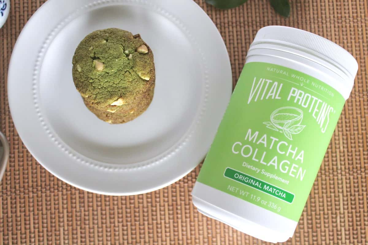 Matcha cookies on a white plate with a tub of match collagen at the side