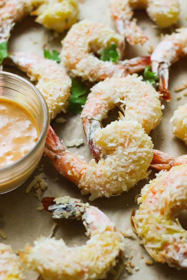 A closse up of pealo coconut lime shrimp with a dipping sauce