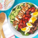 An overhead of a cobb salad sitting on a blue surface with salad servers at the side