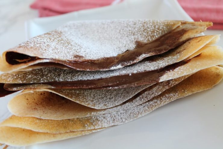 Close up of folded cinnamon sugar crepes with powdered sugar on top
