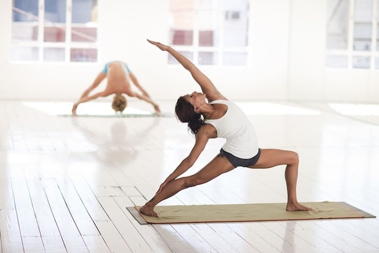 woman doing yoga in a white room