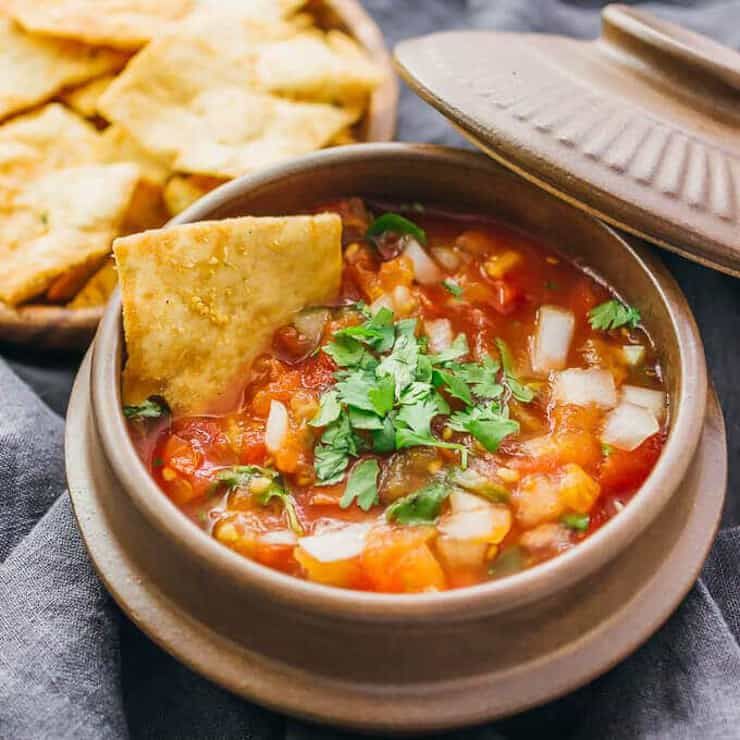 A small bowl filled with Mexican salsa and a chip dipping into it
