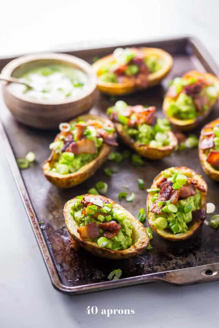 healthy potato skins on a baking tray with toppings an a dip
