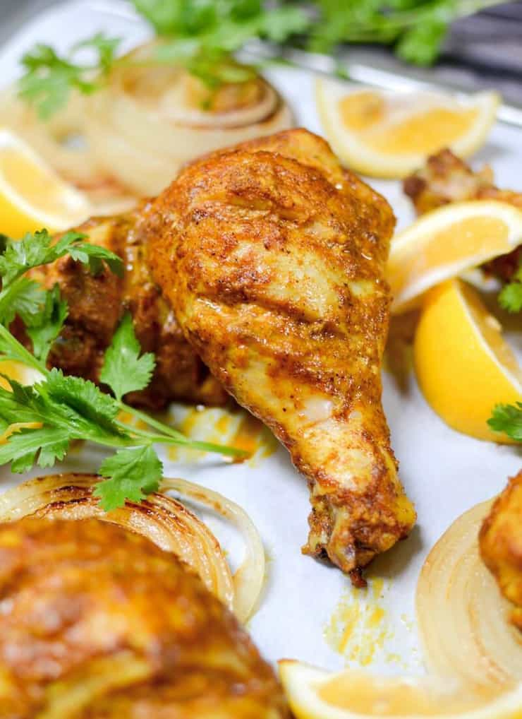 A close up of tandoori chicken on a plate with lemon wedges