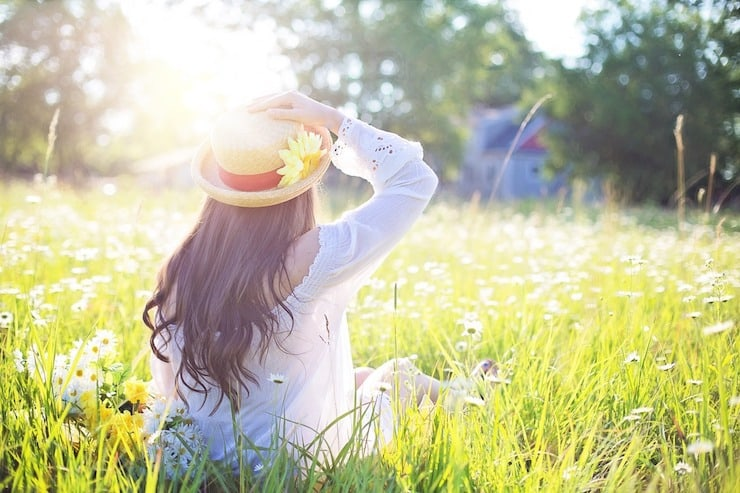 Woman with a hat on sitting in green field