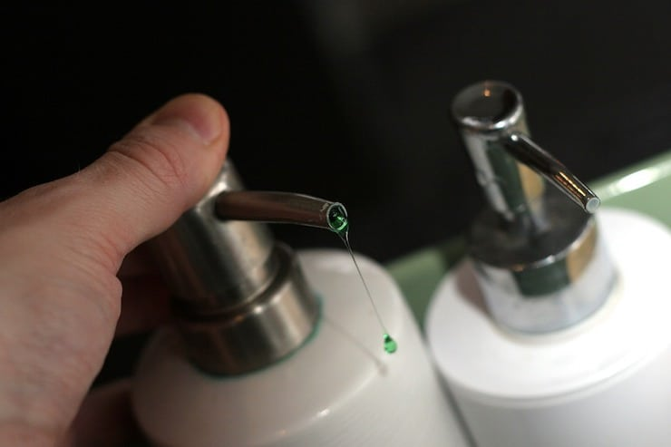 white liquid soap dispenser with green soap coming out