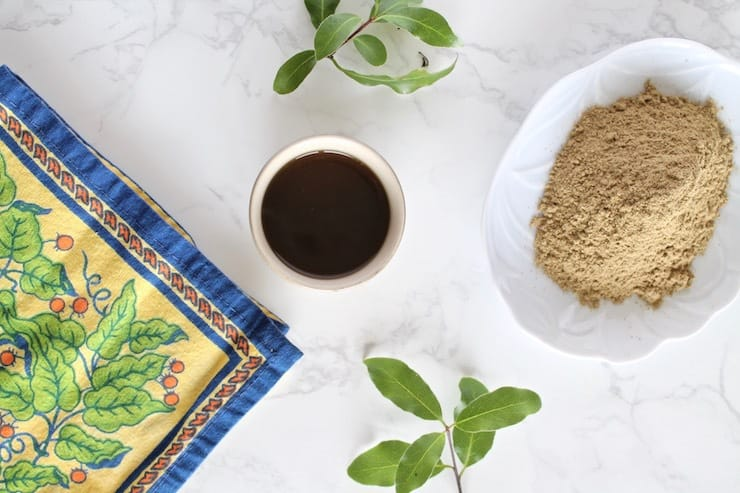Overhead view of cup of essiac tea with powder and floral napkin beside it