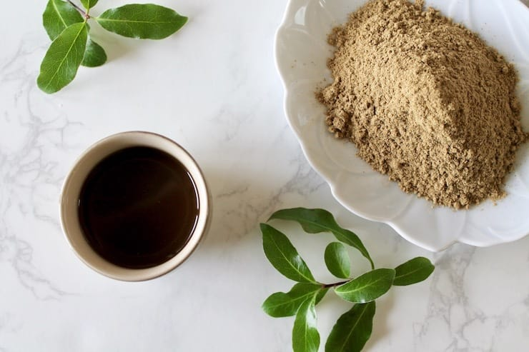Overhead view of cup of essiac tea with powder and leaves beside it