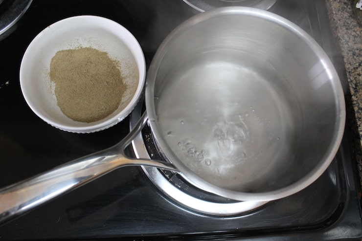 stainless steel pot on the stove with boiling water inside it beside bowl of powdered essiac tea