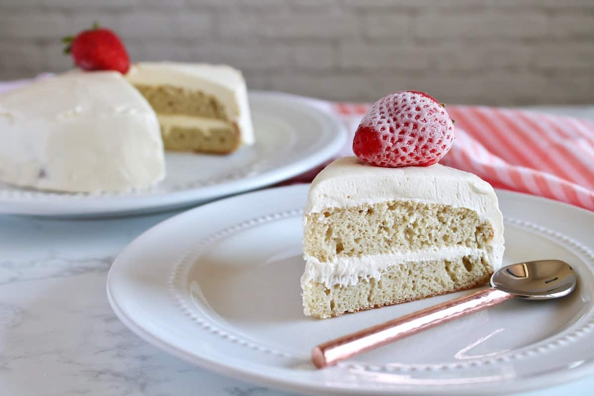Slice of white frosted coconut flour layer cake on small white plate with whole cake in background