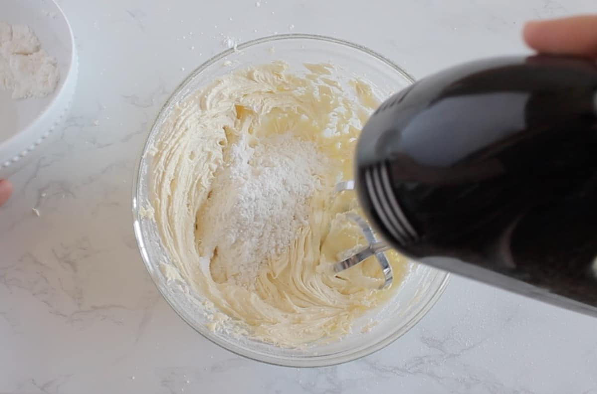 Off white buttercream frosting with confectioners sugar added being blended with electric mixer