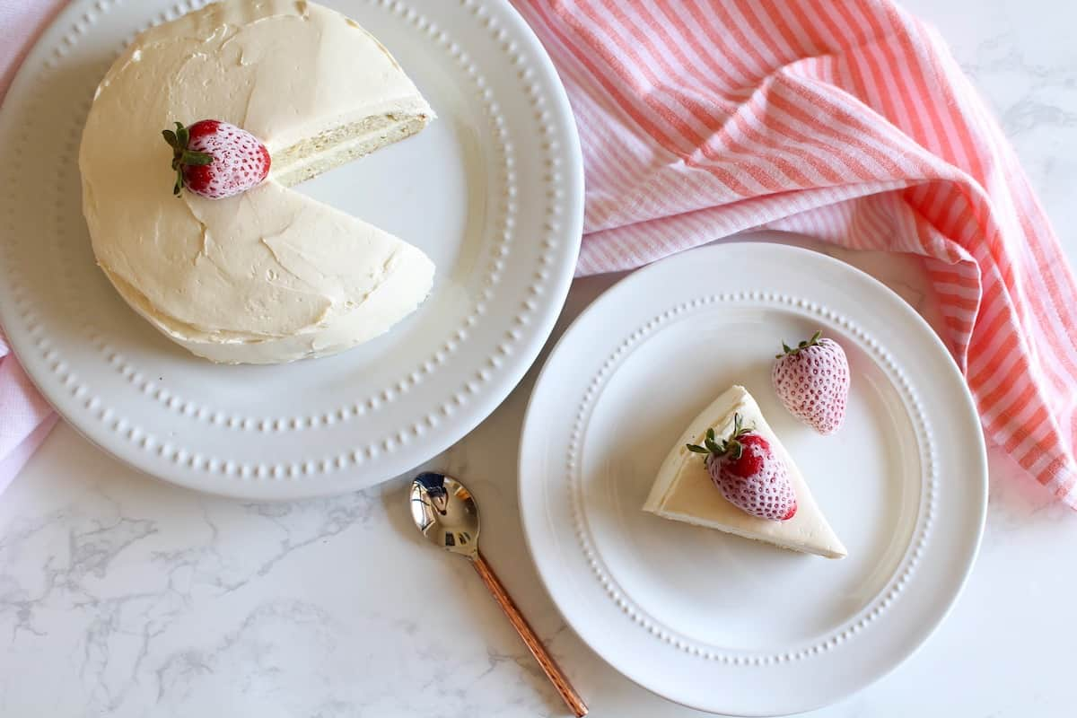 Overhead view of white frosted coconut flour cake with strawberries on top on white plate with slice of cake on smaller white plate next to it