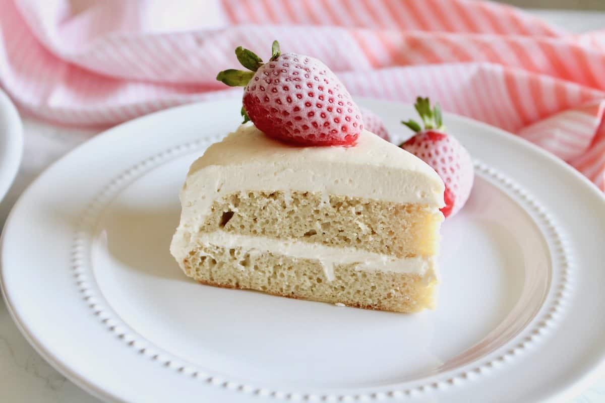 Slice of white frosted coconut flour layer cake on white plate with strawberry on top next to pink striped dish towel