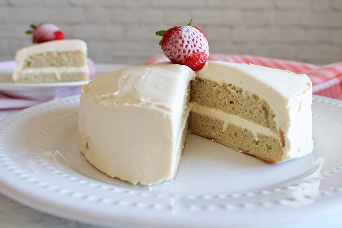 white frosted coconut flour cake with strawberries on top on white plate with slice of cake on smaller white plate behind it
