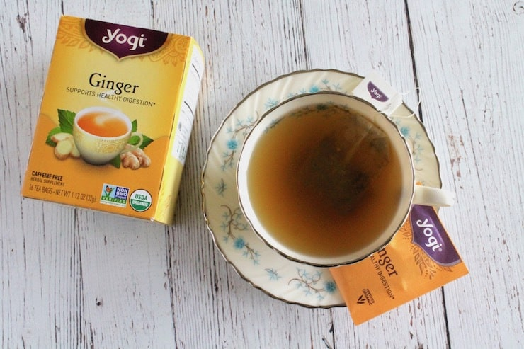 Cup of tea on a saucer with box of ginger tea next to it