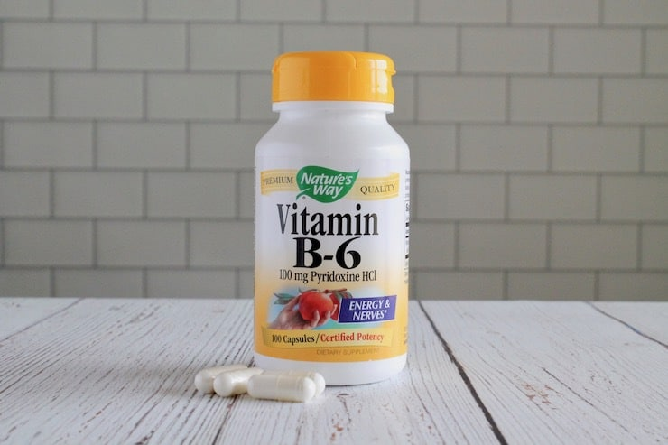 Bottle of vitamin b6 with white capsules next to it on white wooden table