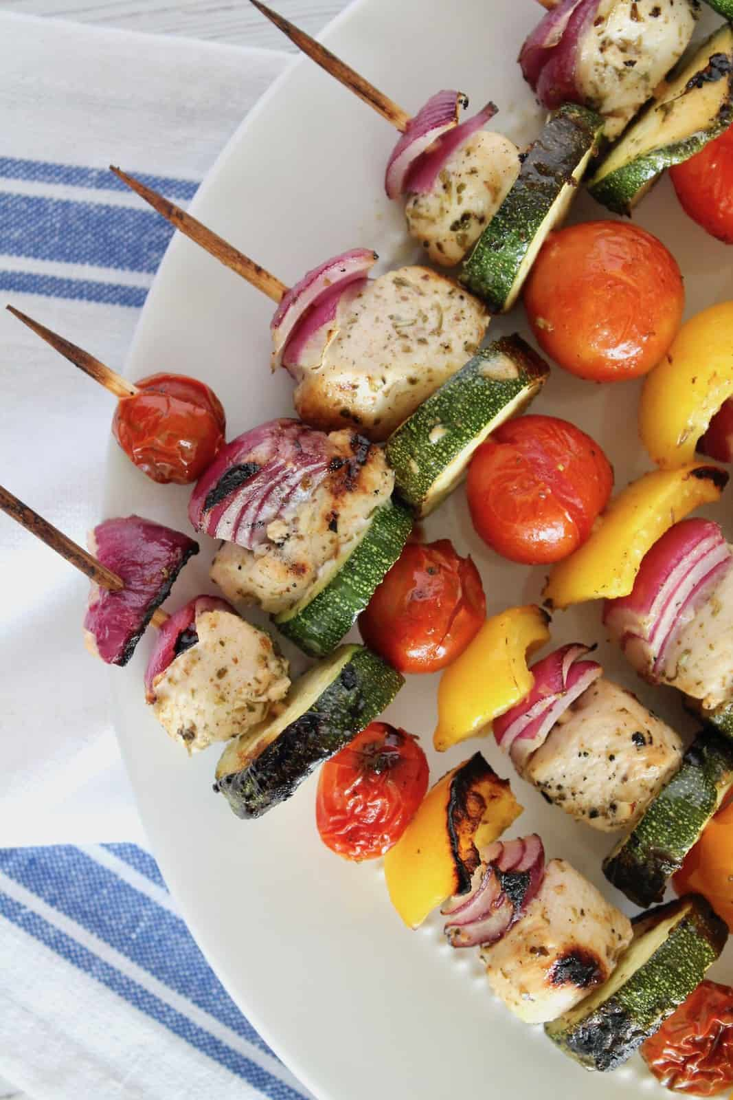 Close up of vegetable and chicken kabobs on wooden skewers on white plate