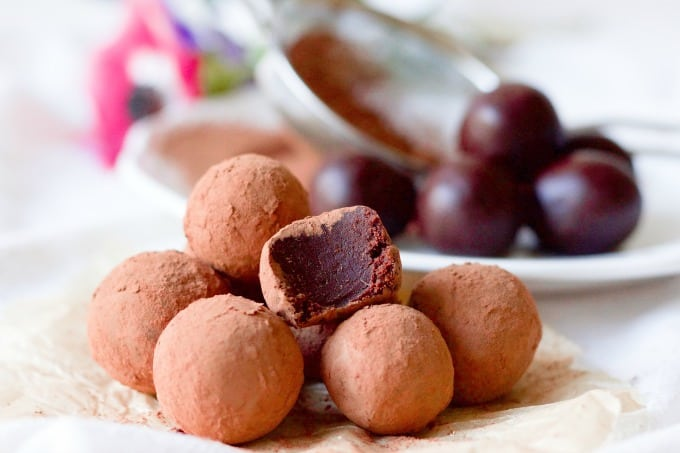 6 chocolate truffles with one with a bite taken out of it on a brown dish towel